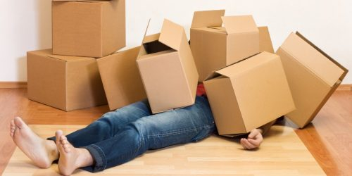 A person under boxes when moving house