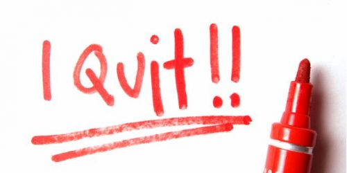 Red pen on white paper with 'I quit' written and underlined twice