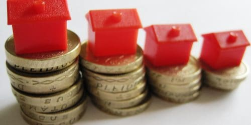 red monopoly houses on stacks on pound coins
