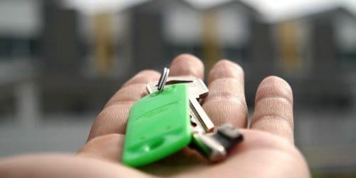 hand holding green house keys